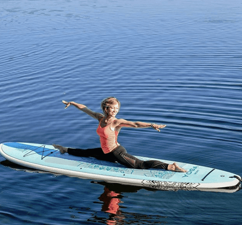 doing paddle board yoga on a lake