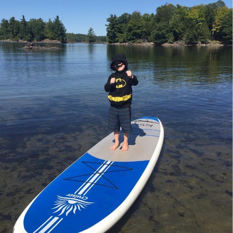 Child dressed as Batman on Paddle Board