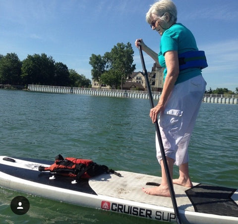 An eldery person riding a SUP