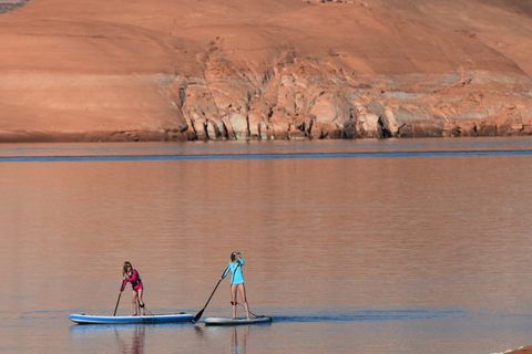 Two kids paddle boarding in calm water