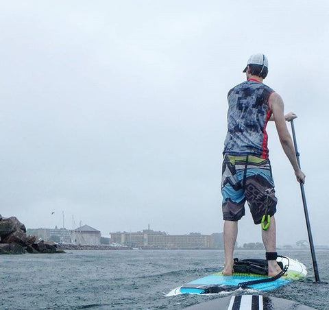 paddle boarding on water near city