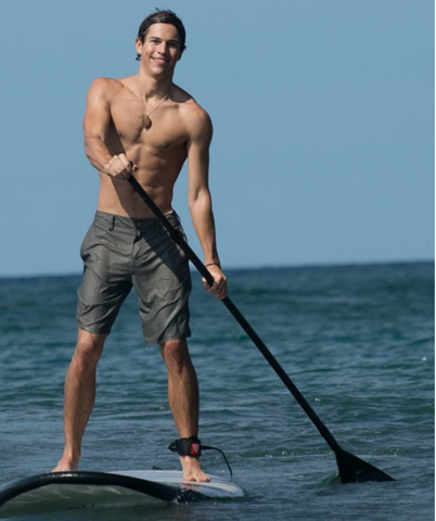 Stand Up Paddle Boarder Wearing a SUP Leash in Calm Water