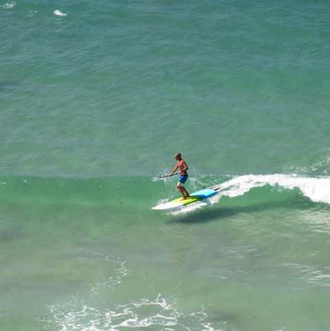 a paddle boarder riding surf