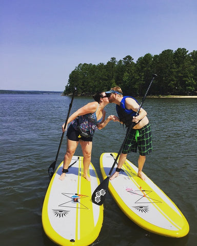 A couple stand up paddle boarding