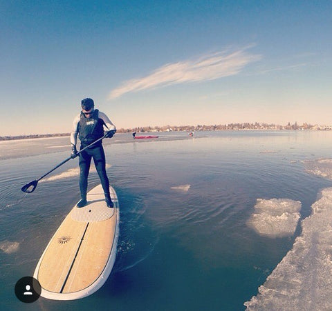 a stand up paddle boarder near ice