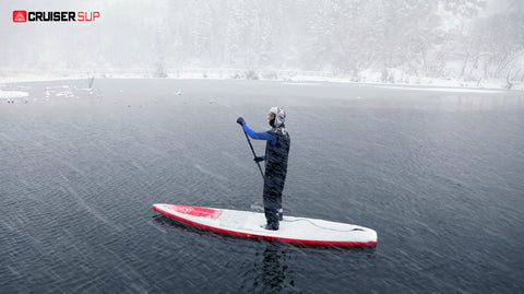 a stand up paddle boarder paddling in winter wearing a SUP leash