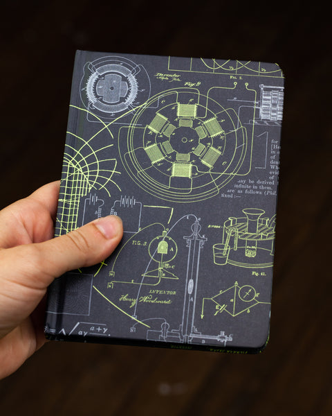 Case study mini hardcover electricity & magnetism recycled notebook pictured in hand by Cognitive Surplus