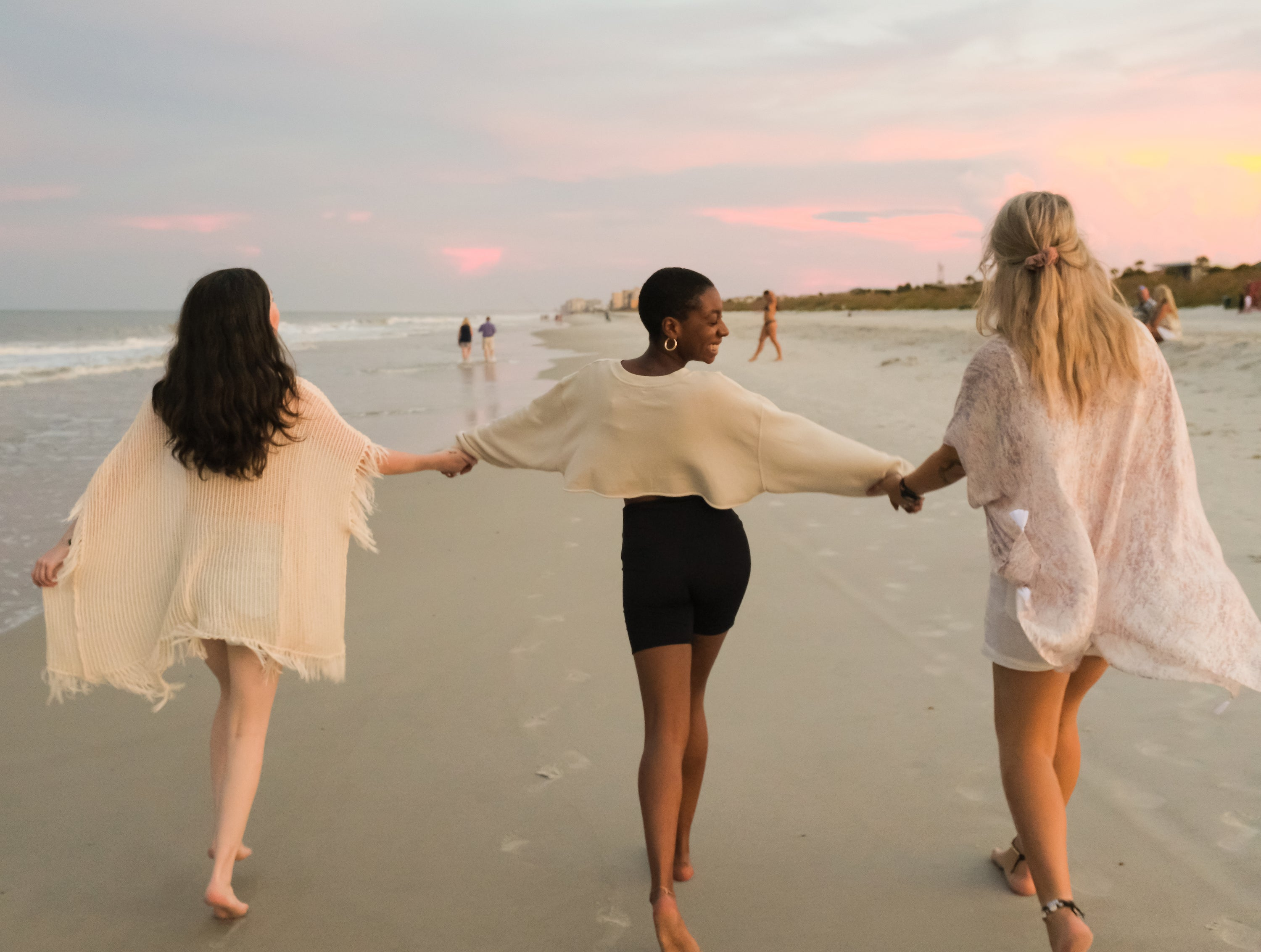 East Coast Beach in the USA at Sunset with three best friends holding hands and skipping down the beach. Pink hues, relaxing vibe.