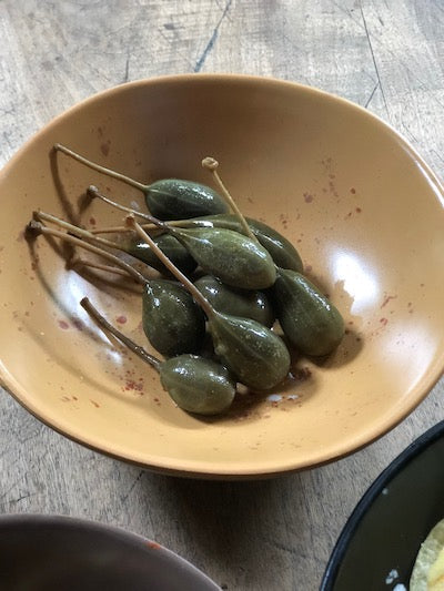 caperberries served in small italian ceramic bowl