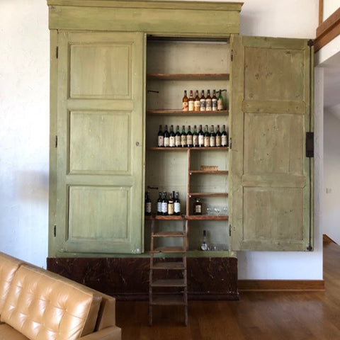 Tuscan Style Home Décor: A Guide The 5 Main Things to Know - A very large 18th century cabinet from MERCATO Antiques bolding defines this space in this room with high ceilings.
