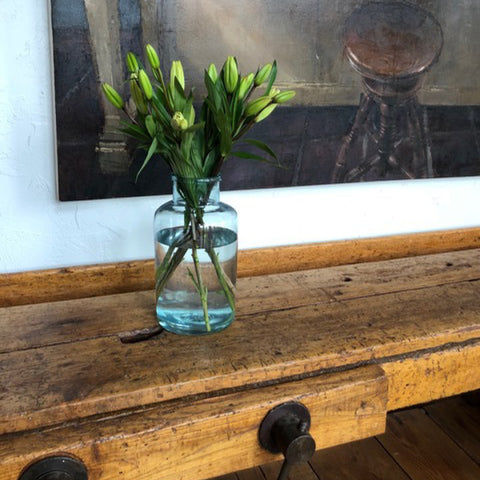 Tuscan Style Home Décor: A Guide The 5 Main Things to Know - An antique Tuscan woodworkers bench which is used for serving when entertaining, and a vintage market jar used as a vase, both from MERCATO Antiques. The student artwork was purchased from The New York Academy of Art.