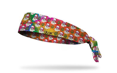 tie dye winter christmas themed headband with repeating pattern of santas wearing rose colored glasses and peace signs