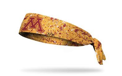 gold headband with maroon paint splatter and University of Minnesota M logo in maroon