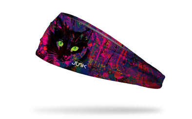 cat themed pink and purple headband with paint splatters and a black cats face with green eyes from center