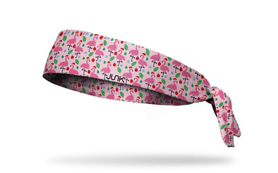 light pink winter christmas themed headband with repeating pattern of flamingos in santa hats ornaments and snowflakes