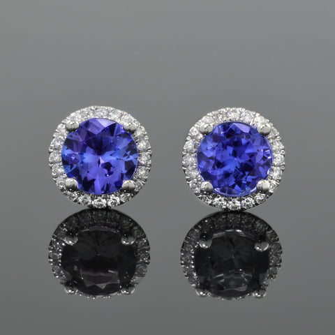 pair of tanzanite stud earrings, each with halo of diamonds.