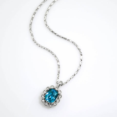 blue zircon pendant with diamonds and vintage style details, set in white gold