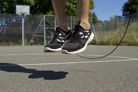 person jumping rope on outdoor basketball court