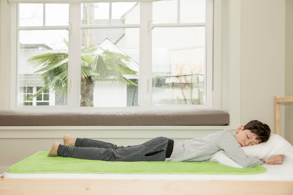 boy sleeping on top of the large PeapodMats bedwetting mat