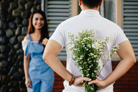 Man holding flowers behind his back in front of woman
