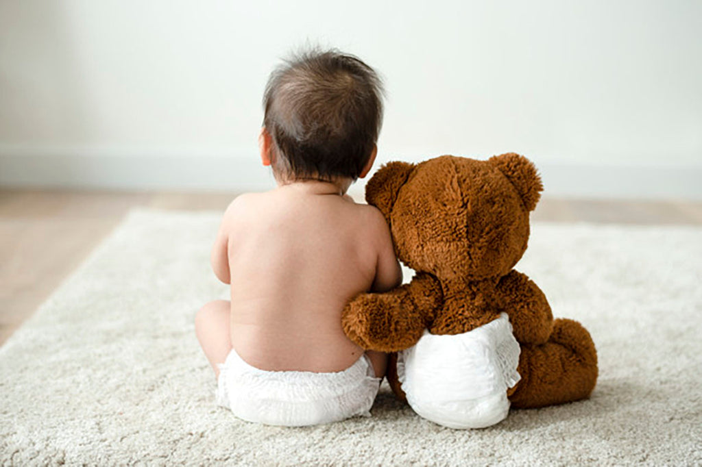 baby in diaper with teddy bear