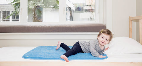 young girl laying on top of PeapodMats on a bed