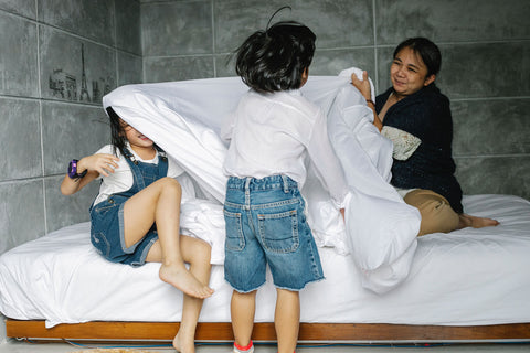 Children playing with bedsheets