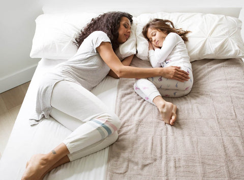 mom & daughter co-sleeping with the PeapodMats incontinence mat