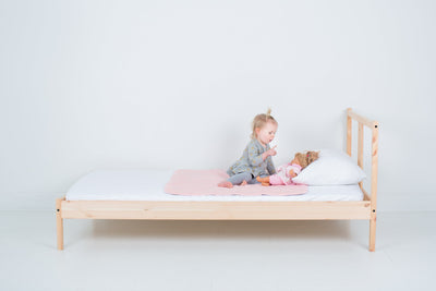 Toddler with Fuzzy Peach colour PeapodMat on a single bed