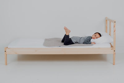 Boy laying on top of medium PeapodMat on a bed