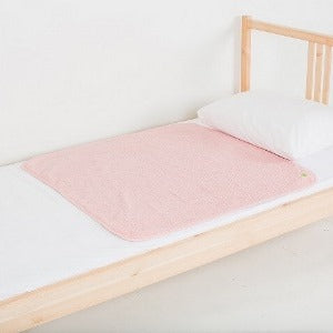 Medium PeapodMat on top of single bed in Fuzzy Peach colour