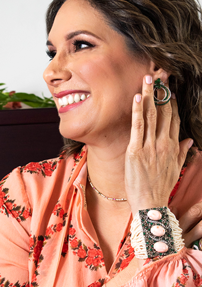 Adriana - Mother at Adriana Fine Jewelry wearing jewelry decorated with emerald, diamonds, coral and pearls