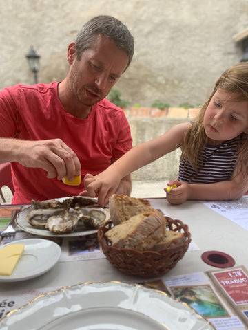 Father and daughter trying oysters