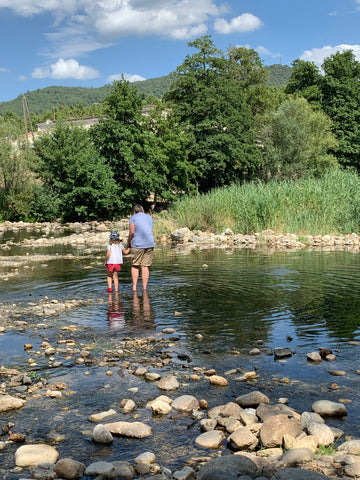 Father and daughter walking in the river in Anduze