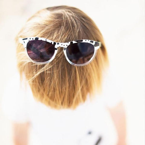 Lifestyle picture of panda printed sunglasses worn on top of child's head as featured on little hotdog watson blog