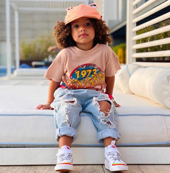 Child wearing sun hat in coral sat on a bench