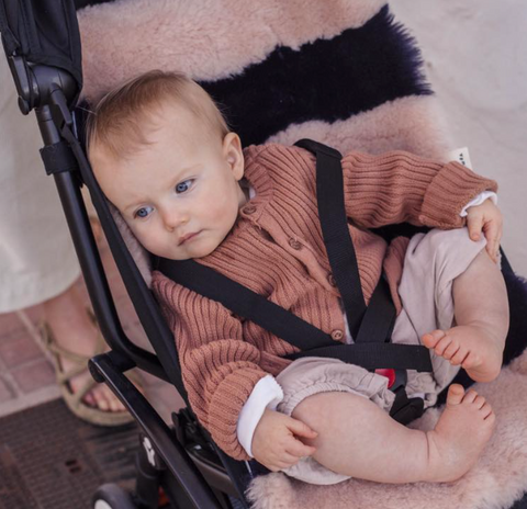 Baby in push chair with striped sheepskin Bini Bamba pram liner