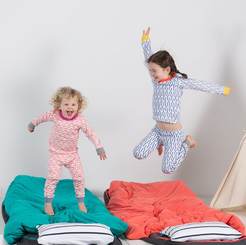 Two kids jumping up and down on Bundle Beds camping beds
