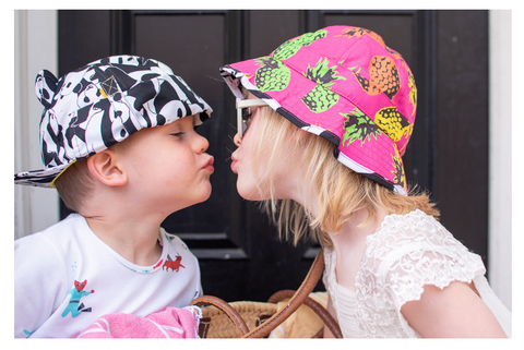 Boy and girl kissing wearing little hotdog watson sun hats