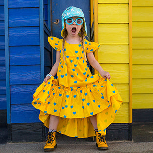 Child wearing Little Hotdog Watson sundress in front of yellow and blue beach hut