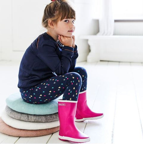lifestyle image of girl wearing hot pink wellington boots