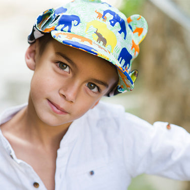 Boy wearing elephant print sun hat with neck flap rolled up by Little Hotdog Watson