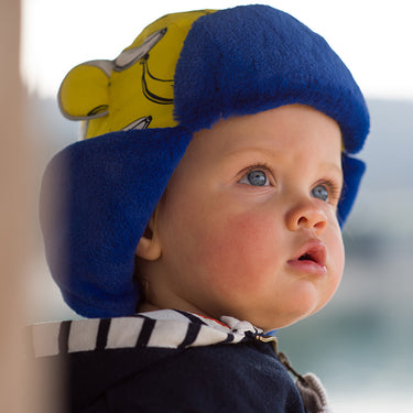 baby wearing a banana print fur trapper hat