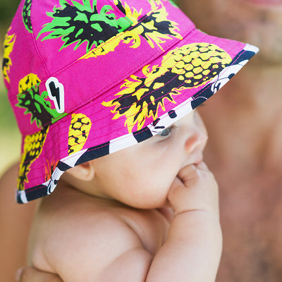Lifestyle photo of baby in floppy sunhat Little Hotdog Watson pionner in print pineapple punch