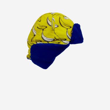 flat lay of banana print arctic cub hat with flaps up