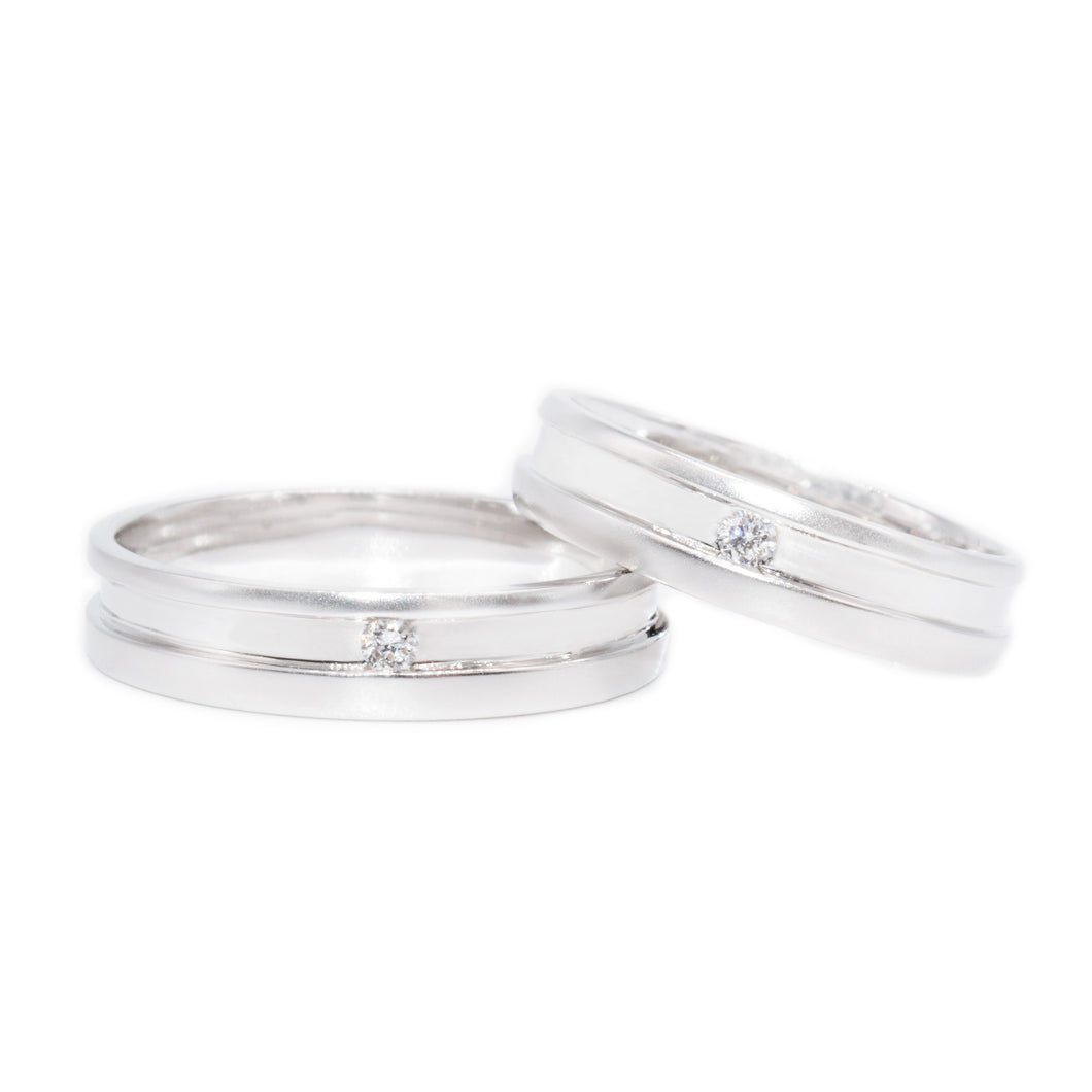 18 carat white-gold off center single diamond wedding band set