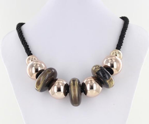 Chunky, polished stone necklace with metallic accents on a braided strand.