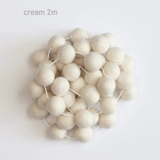 felt garland of round balls, colour cream