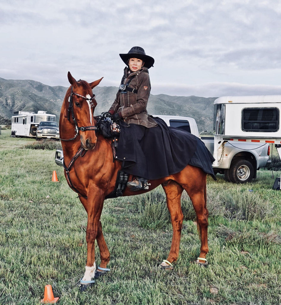Dawn Champion posing on her brown horse wearing blue Scoot Boots