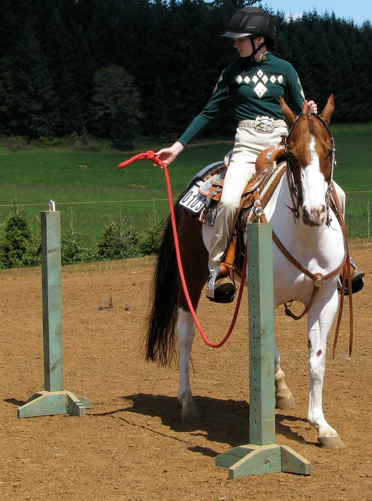 A girl in a green jumper desensitising a horse using a gate obstacle on a sand arena